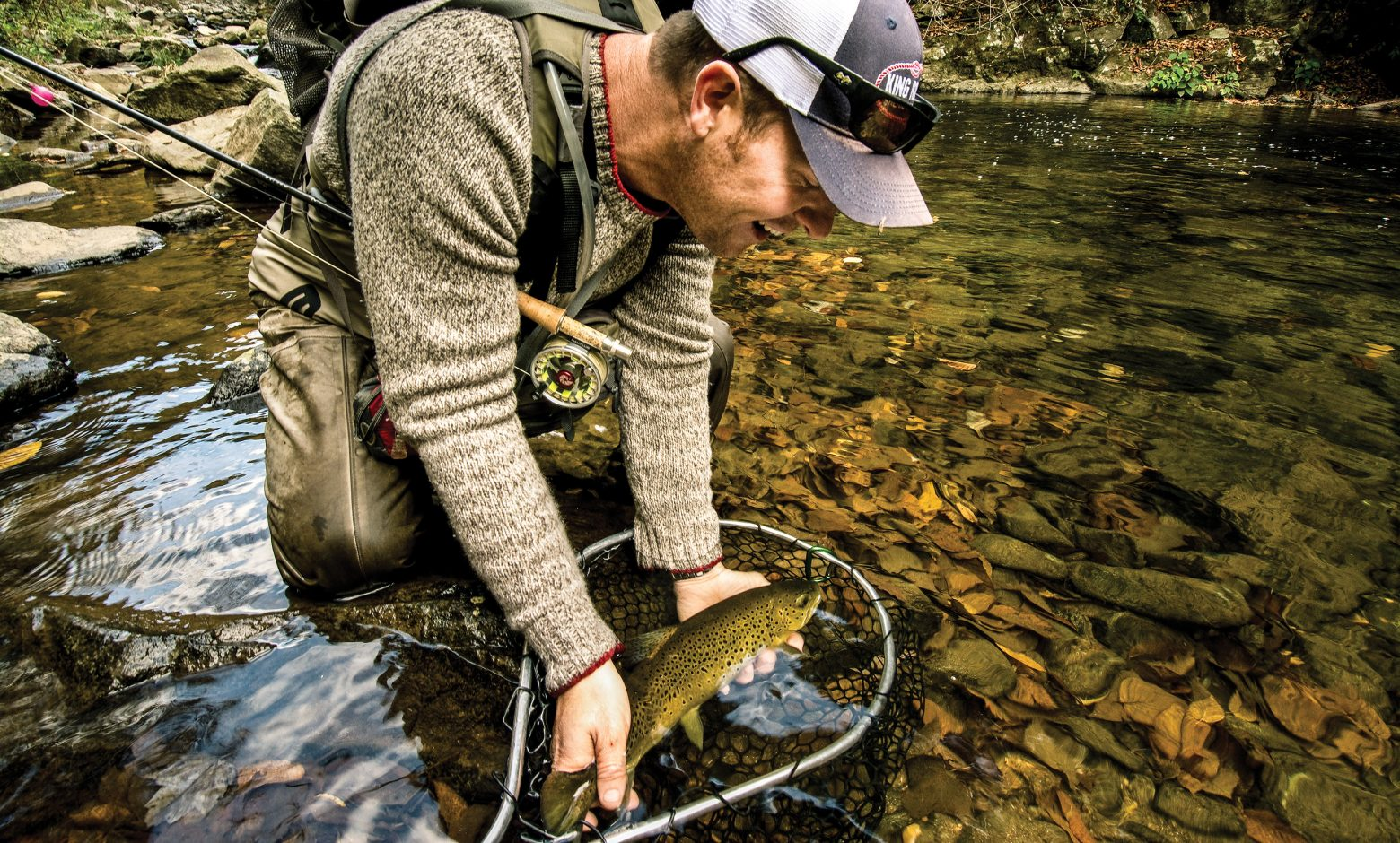 Man holding brown trout in a net