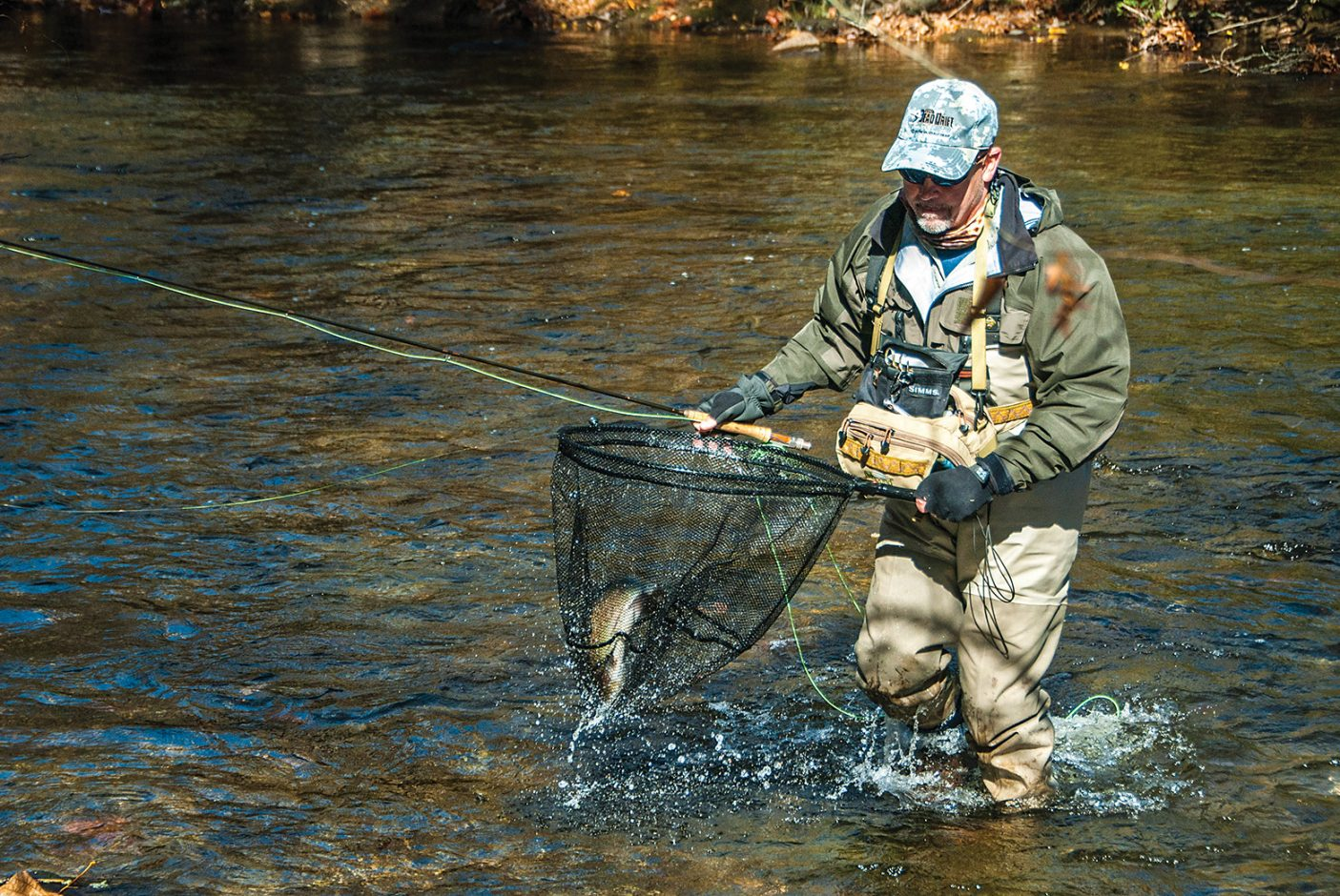 Man in river with fly rod and trout in net